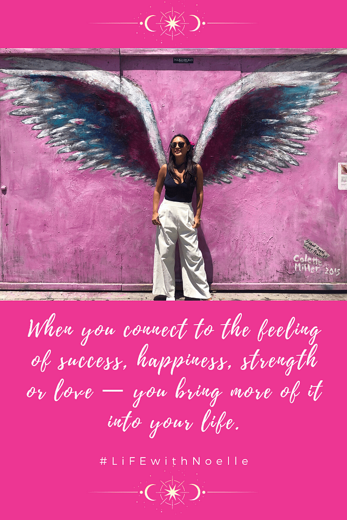 """Noelle leaning on a painted wall with angel wings with a quote, """"When you connect to the feeling of success, happiness, strength, or love-- you bring more of it into your life."""